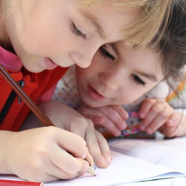 Děti kreslící do sešitu hnědou pastelkou