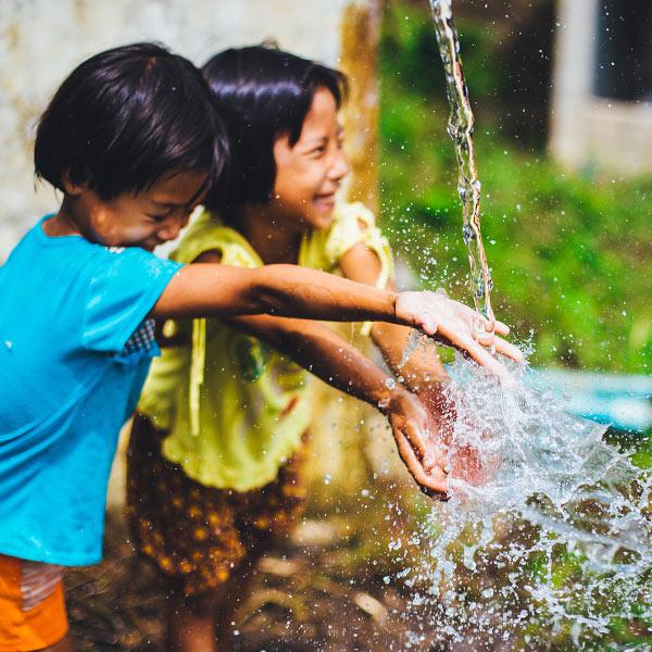 Děti hrající si u tekoucí vody